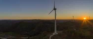 Aerial Wind farm turbines silhouette at sunset. Clean renewable energy power generating windmills. Stock Photo