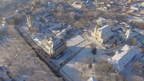 Aerial of winter suburbs at residential, historic and religious buildings. Winter aerial shot of the Zhytomyr city suburbs snow sunset residential, historic and stock video