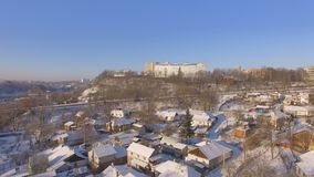 Aerial of winter suburbs at residential, historic and religious buildings. Winter aerial shot of the Zhytomyr city suburbs snow sunset residential, historic and stock footage