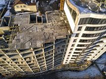 Aerial winter top view of modern developing city with tall apartment complex building under construction, parked cars, roofs and. Streets. Urban infrastructure stock photo