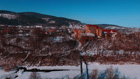 Aerial winter view high above rural village surrounded by pine tree forest. Winter river, flying on quadrocopters. Ski resort. Karpaty, Ukraine stock footage