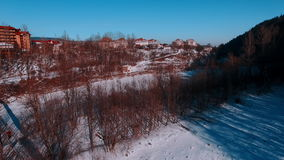Aerial winter view high above rural village surrounded by pine tree forest. Winter river, flying on quadrocopters. Ski resort. Karpaty, Ukraine stock video footage
