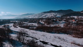 Aerial winter view high above rural village surrounded by pine tree forest. Winter river, flying on quadrocopters. Ski resort. Karpaty, Ukraine stock video