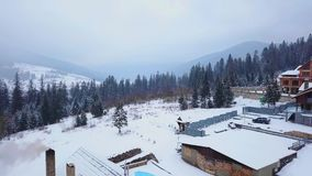 Aerial of wooden cottages in mountain village surrounded with coniferous forest. Drone view of chalets covered with snow stock video footage