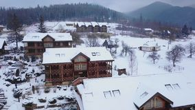 Aerial of wooden cottages in mountain village surrounded with coniferous forest. Drone view of chalets covered with snow stock video