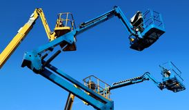 Aerial working platforms of cherry picker against blue sky.  stock photo