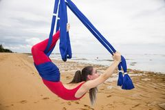 Aerial yoga or Anti-gravity yoga. Young woman practicing fly yoga asana outdoors stock image