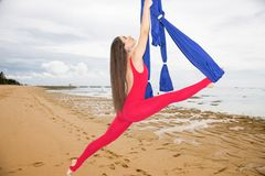 Aerial yoga or Anti-gravity yoga. Young woman practicing fly yoga asana outdoors royalty free stock image