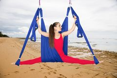 Aerial yoga or Anti-gravity yoga. Young woman practicing fly yoga asana outdoors stock photography