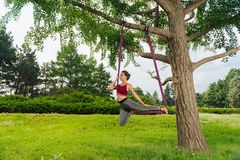 Athletic fit woman performing anti-gravity asana in nature. Aerial yoga. Professional yoga woman performing aerial yoga on warm pleasant summer morning royalty free stock photos