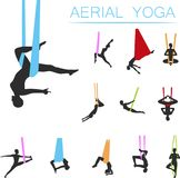 Aerial yoga set with young woman silhouettes. In different yoga poses. Girl doing anti gravity yoga exercises in hammocks. Female fitness practice, sport and Stock Photo
