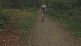 Aerial of a young woman walking through a forest, low altitude close tracking shot backwards then ascenting over her. Aerial of a young woman walking through a stock footage