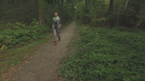 Aerial of a young woman walking through a forest, low altitude tracking shot backwards. In front of the woman then letting her pass to the right, medium shot stock video