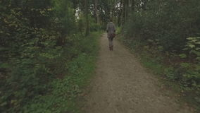 Aerial of a young woman walking through a forest, low altitude tracking shot forward following. Starting with  a long shot then coming closer steadily stock video footage