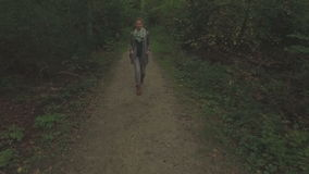 Aerial of a young woman walking through a forest, low altitude tracking shot from left to right. Aerial of a young woman walking through a forest, low altitude stock footage