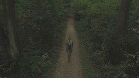 Aerial of a young woman walking through a forest, slow descent between trees  and tracking shot backwards. In front of the woman, long shot stock footage