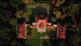 AERIAL zoom out of Castle. Flight over beautiful castle; located in landscape park with green trees forests in autumn. 4K. Castel stock footage