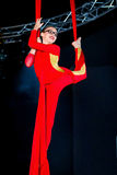 Aerialist Doing a Rebecca Split. A young aerialist does a Rebecca Split during a rehearsal. She is in vibrant red and wearing glasses. The aerial silk is red as Royalty Free Stock Photography