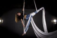 Aerialist doing tricks on silks. Aerialist woman doing some flexibility and strength tricks on silks Stock Photo