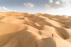 Aeril view of Liwa desert, part of Empty Quarter, the largest co. Aerial view of Liwa desert in Abu Dhabi and person standing in the dunes stock photography