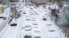 Aerila view of snow-covered cars stand in the parking lot on a winter day Royalty Free Stock Photos