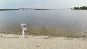 Aero, όμορφα newlyweds που στέκεται στην παραλία, με τα ποτήρια της σαμπάνιας και κάτω από μια διαφανή ομπρέλα, ενάντια φιλμ μικρού μήκους