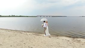 Aero, beautiful newlyweds walking along the beach, under a transparent umbrella, against the blue sky, river, and a. Large bridge over the river. spring sunny stock video