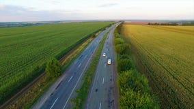 Aero flyg över vägen mellan fält i solnedgång arkivfilmer