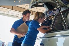 Aero- ingeniero And Apprentice Working en el helicóptero en hangar Imagen de archivo libre de regalías