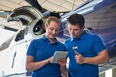 Aero Ingenieur And Apprentice Working auf Hubschrauber im Hangar-Klo Lizenzfreie Stockbilder