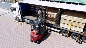 Aero, pakhuizen Het leegmaken van de vrachtwagen het leegmaken van goederen van de vrachtwagen aan het pakhuis De vorkheftruck ze stock video