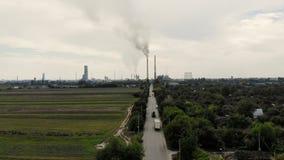 Aero w środku pole, droga z samochodami dwa wysoki, duży, dymi kominy to prowadzi wielka roślina gray dymu zbiory