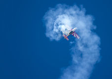Aerobatic aircraft in a spin. Nice white smoke against a blue sky stock image