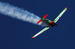 Aerobatic airplane. Approaching with white smoke trail royalty free stock photography