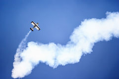 Aerobatic. An airplane is doing aerobatic on the sky stock photography