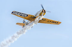 Aerobatic airplane pilot Jurgis Kairys training in the sky of the city. Colored airplane with trace smoke, airbandits, aeroshow Royalty Free Stock Images