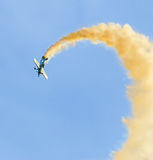 Aerobatic airplane pilot Jurgis Kairys training in the sky of the city. Colored airplane with trace smoke, airbandits, aeroshow Royalty Free Stock Photo