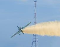 Aerobatic airplane pilot Jurgis Kairys training in the sky of the city. Colored airplane with trace smoke, airbandits, aeroshow Stock Photos