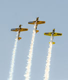 Aerobatic airplane pilots training in the sky of the Bucharest City, Romania. Colored airplane with trace smoke Royalty Free Stock Photography
