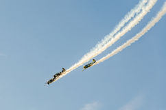 Aerobatic airplane pilots training in the sky of the Bucharest City, Romania. Colored airplane with trace smoke Stock Image