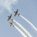 Aerobatic airplane pilots training in the sky of the Bucharest City, Romania. Colored airplane with trace smoke Stock Images