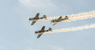 Aerobatic airplane pilots training in the sky of the Bucharest City, Romania. Colored airplane with trace smoke Royalty Free Stock Images