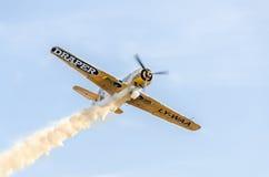 Aerobatic flygplanpilotJurgis Kairys utbildning i himlen av staden Kulört flygplan med spårrök, airbandits, aeroshow arkivfoto