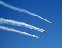 AEROBATIC HARVARD TEAM TRAILING SMOKE. Aerobatic Harvard team trailing white smoke royalty free stock image