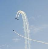 Aerobatic Piloten mit ihren farbigen Flugzeugen ausbildend im blauen Himmel Stockfotos