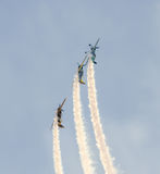 Aerobatic pilots with her colored airplanes training in the blue sky Stock Image