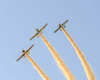 Aerobatic pilots training in the blue sky, airplanes with colored trace smoke Stock Photos