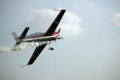 Aerobatic plane trailing smoke. Single engine aerobatic plane trailing smoke from underneath stock photography