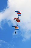 Aerobatic skydiving. Three skydivers descending on top of one another parachute in canopy aerobatic maneuver stock image