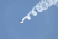 Aerobatic stunt. Airplane performing aerobatic stunt with smoke trail royalty free stock images
